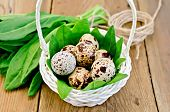 pic of sorrel  - Quail eggs in a white wicker basket with sorrel a coil of rope on the background of wooden boards - JPG