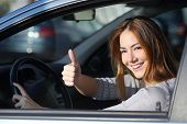 image of driving school  - Happy woman inside a car driving in the street and gesturing thumb up - JPG