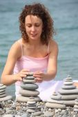 Young Woman Builds  Stone Stacks On Pebble Beach