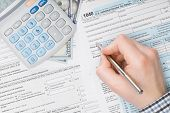 stock photo of irs  - Man filling out 1040 US Tax Form  - JPG