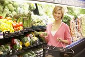 stock photo of supermarket  - Woman shopping in supermarket - JPG