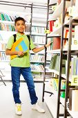 foto of book-shelf  - Standing boy with books in school library putting book on the shelf - JPG