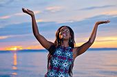 picture of black american  - Portrait of beautiful black African American woman posing with open hands up to the sky on the beach at sunset - JPG