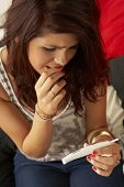 stock photo of teen pregnancy  - Teenage girl with pregnancy test - JPG