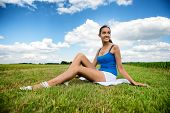 picture of leggy  - Beautiful slender tanned leggy young girl in shorts sitting relaxing in a green field in the warm summer sunshine - JPG