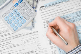 pic of cpa  - Man filling out 1040 US Tax Form  - JPG