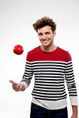 image of throw up  - Happy casual young man throwing an apple up - JPG