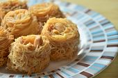 stock photo of baklava  - Closeup of birds nest baklava dessert with peanuts - JPG