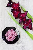 picture of gladiolus  - maroon gladiolus and jelly candies on a light wooden background - JPG