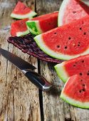 picture of food crops  - cut pieces of ripe juicy watermelon in a wicker vase on old wooden background - JPG