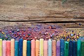 foto of pigment  - Pastel crayons and pigment dust on old wooden background - JPG