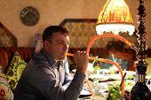 picture of hookah  - Man smoking hookah in the arabic restaurant  - JPG