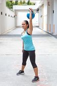 picture of snatch  - Beautiful sporty hispanic woman in blue  lifting blue kettlebell  for snatch routine outdoors - JPG