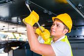 stock photo of motor vehicles  - Asian motor mechanic working on construction or mining machinery in vehicle workshop - JPG