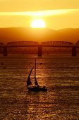 stock photo of portland oregon  - Small sailboat tacking back into port on the Columbia River near Portland Oregon at sunset with Interstate 5 bridge in background - JPG