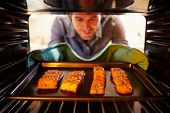 image of oven  - Man Putting Salmon Fillets Into Oven To Cook - JPG