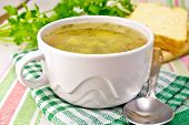 picture of green pea  - Green pea soup in a white bowl on a green napkin bread spoon parsley on a background of a linen napkin - JPG