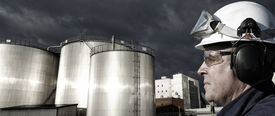 picture of refinery  - refinery worker with giant fuel storage tanks at sunset - JPG