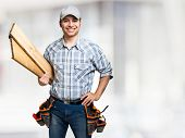 picture of carpenter  - Portrait of a smiling carpenter holding wood planks - JPG