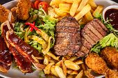 picture of leafy  - Wholesome platter of mixed meats including grilled steak crispy crumbed chicken and beef on a bed of fresh leafy green mixed salad served with French fries and chutney or BBQ sauce in a dish - JPG