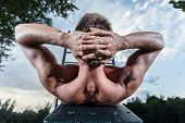 pic of abdominal muscle  - Athlete in park excercises his abdominal muscles - JPG