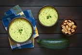 pic of zucchini  - Overhead shot of two rustic bowls of cream of zucchini soup garnished with parsley leaf with a bowl of homemade croutons and a raw zucchini on the side photographed on dark wood with natural light - JPG