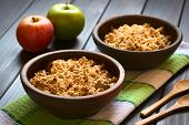 picture of crisps  - Two rustic bowls of baked apple crumble or crisp on kitchen towel wooden spoons and fresh apples on the side photographed on dark wood with natural light  - JPG