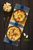 picture of dark side  - Overhead shot of savory baked vegetarian bread pudding made of zucchini bell pepper tomato and diced baguette seasoned with thyme and parsley in rustic bowls on kitchen towel ingredients and wooden spoons on the side photographed on dark wood with natural - JPG