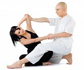picture of thai massage  - Young female sitting and receiving traditional thai arm stretching massage by therapist isolated on white - JPG