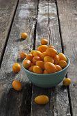 image of kumquat  - freshly kumquats on a rustic wooden table - JPG