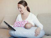 stock photo of breast-milk  - Happy mother breast feeding her newborn in room indoor - JPG