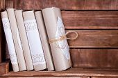 foto of book-shelf  - Wood book shelf with old book heap and candle in rustic style - JPG