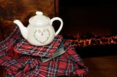 picture of cozy hearth  - A teapot on a book by the fireplace in a cold winter night - JPG