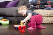 picture of color wheel  - one year age blonde lovely cute caucasian white baby grey shirt pink trousers and shocks playing with wheel wooden colors toys indoor on brown floor - JPG