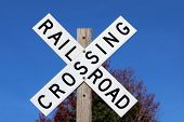 image of railroad-sign  - Railroad crossing sign against blue sky background - JPG