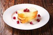 picture of curd  - curd pudding with raspberries on a white plate - JPG