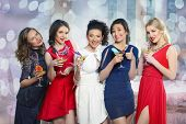 foto of cheers  - Cheerful girls clinking glasses of cocktails at the party - JPG