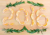 image of section  - 2016 number written with oranges sections and rosemary sprigs on wooden background - JPG