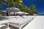 stock photo of boracay  - Sun umbrellas and beach beds on tropical coastline Philippines Boracay - JPG
