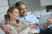 pic of married couple  - Mature couple relaxing in sofa and using digital tablet - JPG