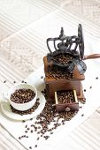 stock photo of coffee coffee plant  - white tablecloth on the table or burlap old coffee grinder filled with coffee beans next to a white porcelain cup filled with coffee beans two croissants - JPG