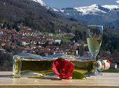 foto of liquor bottle  - the liquor bottle with lying near the red flower and the full glass - JPG