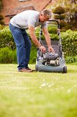 picture of grass-cutter  - Man Working In Garden Cutting Grass With Lawn Mower - JPG