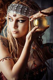 stock photo of divine  - Magnificent fortune teller holding crystal ball - JPG