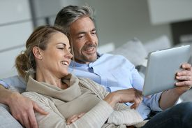 pic of mature adult  - Mature couple relaxing in sofa and using digital tablet - JPG