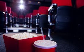 stock photo of cinema auditorium  - Empty rows of red seats with pop corn and drink on the floor at the cinema - JPG