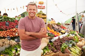 stock photo of stall  - Male Stall Holder At Farmers Fresh Food Market - JPG