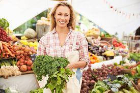 foto of stall  - Female Stall Holder At Farmers Fresh Food Market - JPG