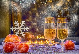 foto of champagne color  - glasses of champagne candles and tangerines in the winter window background - JPG