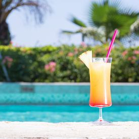 stock photo of cinderella  - Glass of Cinderella kids cocktail on the pool nosing at the tropical resort - JPG